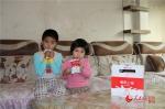 15日,乌鲁木齐市沙依巴克区扬子江路汇月社区学龄前小朋友领到工作人员专门送来的牛奶欣喜万分。胡宝军 摄 - 人民网