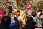 游客和罗布人村寨景区里的人一起跳舞。 庞博 摄 - 中国新疆网